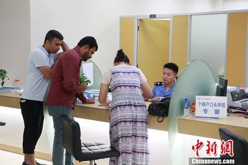 资料图:2018年8月中旬,2名外商正在助理的协助下办理业务。<a target='_blank' href='http://www.chinanews.com/'>中新社</a>发 刘佩琦 摄