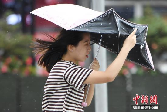 资料图:市民的雨伞被大风掀翻。张瑶 摄