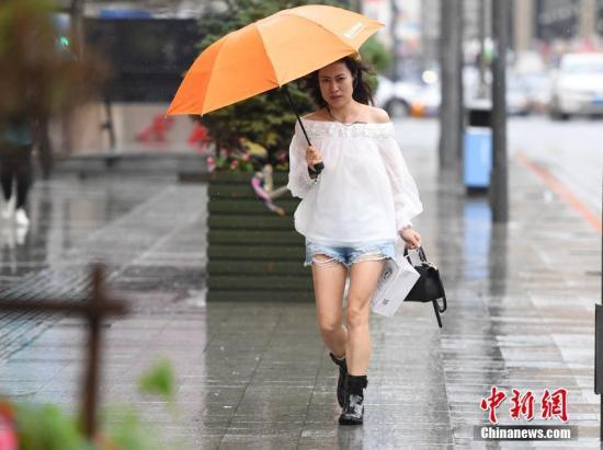 资料图:台风中市民打伞出行。张瑶 摄