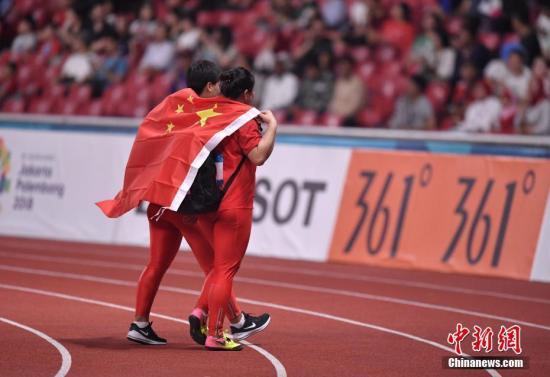 """国际赛场,""""重量级天团""""是中国田径最有竞争力的团队。(资料图:图为:图为雅加达亚运会王峥、罗娜身披国旗向教练及到场的中国观众致谢。<a target='_blank' href='http://curtain-corner.com/'>中新社</a>记者 李霈韵 摄)"""