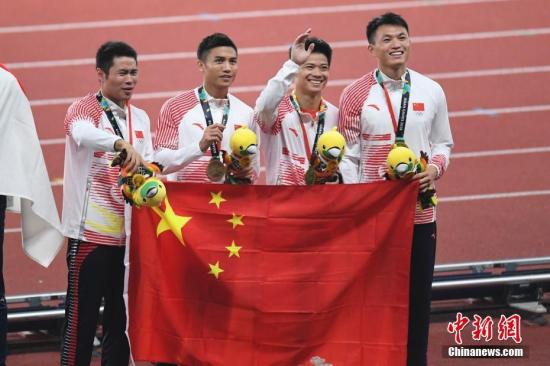 资料图:雅加达亚运会上,中国代表团在田径项目获得12枚金牌,与巴林队持平。图为中国队选手登上领奖台向观众招手致意。<a target='_blank' href='http://www.chinanews.com/'>中新社</a>记者 杨华峰 摄