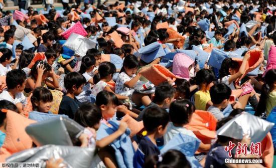 """当地时间8月31日,日,本""""防。灾日""""前一天,东京一所小学举行地震模拟演习。为纪念1923年9月1日发生的关东大地震,日,本政府于1960年将每年9月1日定为""""防。灾日""""。"""