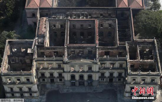 """当地时间2018年9月3日,巴西里约热内卢,发生大火后的巴西国家博物馆。当地时间9月2日晚,位于巴西里约的巴西国家博物馆发生火灾。拥有200年历史的巴西国家博物馆陷入火海,2000万藏品受到威胁,其中包括埃及文物和巴西最古老的人类化石等。巴西总统特梅尔表示,博物馆藏品被烧毁,造成""""无可估量""""的损失,失去了200年的研究和知识,这是""""悲伤的一天""""。"""