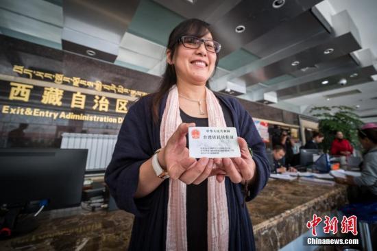 9月5日,拉萨市的台胞余女士展示自己刚领到的台湾居民居住证。当日,西藏自治区公安厅出入境管理总队办证大厅举行港澳台居民居住证发放仪式,在藏台胞余女士领到了她的台湾居民居住证,这也是西藏自治区发出的第一张台湾居民居住证。9月1日,《港澳台居民居住证申领发放办法》正式实施,符合申领条件的港澳台居民,根据本人意愿,可以申请领取居住证。何蓬磊 摄