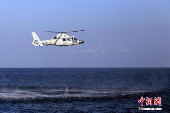 图为黄山舰舰载直升机施放声纳。 /p发 徐广 摄
