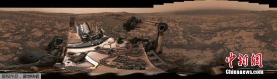 """好奇号在其所在的薇拉・鲁宾岭(Vera Rubin Ridge)拍摄了一张360度的全景""""自拍"""",揭示空气中依然飘浮着一层薄薄的尘埃。褐色的天空、远处的山、古老的湖床痕迹,以及好奇号火星车的自拍。"""