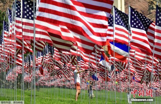 """当地时间2018年9月10日,游客在美国加利福尼亚马里布佩珀丁大学参观""""国旗飘扬""""展览。该展览每年举行,其展出的2997面国旗是为了纪念2001年9月11日""""911""""恐怖袭击的受害者."""