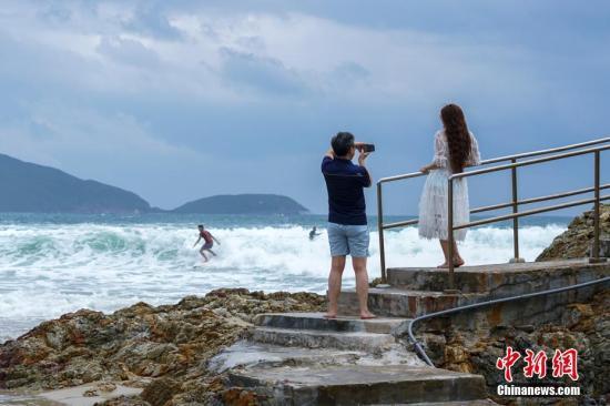 12日,位于香港岛东部的大浪湾浪高风急,大风大浪吸引游客在海边留影。 中新社记者 张炜 摄