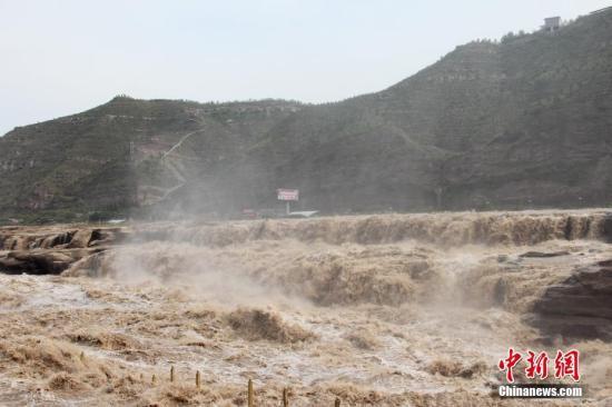 """资料图:黄河壶口瀑布水量大增,湍急的水流携带大量的泥沙奔涌而下,主瀑布几乎没有落差,出现""""水岸齐平""""的景象。 阿琳娜 摄"""