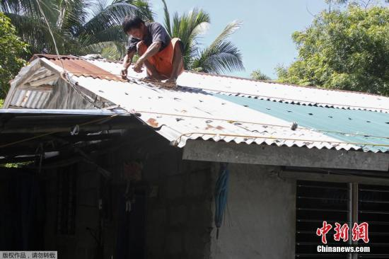 """当地时间9月13日,菲律宾伊洛科斯省居民加固房屋,为抵御即将到来的超强台风""""山竹""""做准备。"""