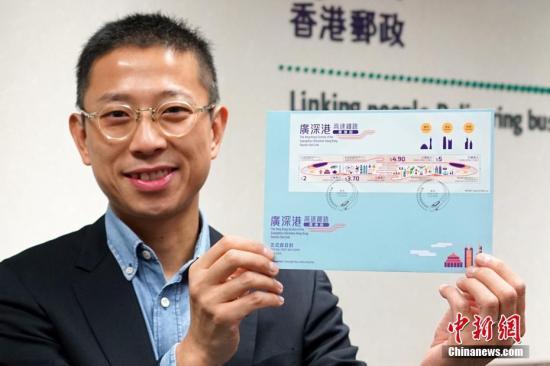 """9月13日,距离广深港高铁正式通车还有10天,香港邮政举行记者会,宣布一套以""""广深港高速铁路香港段""""为主题的特别邮票及相关集邮品将于9月17日推出发售,以资纪念。这套邮票形象鲜明,以高铁列车的夺目颜色和流线设计贯串四枚邮票,并由左至右分别展示广州、深圳和香港的特色。邮票上的列车有代表广、深、港三地文化和地标的图案,列车中段更化成两只牵着的手,象征香港与内地在经济及其他方面的交流,将随着广深港高铁香港段通车后更为密切,携手开拓新机遇。图为香港邮政高级经理李振宇展示贴有特别邮票小全张并以特别邮戳盖销的首日封。记者 张炜 摄"""