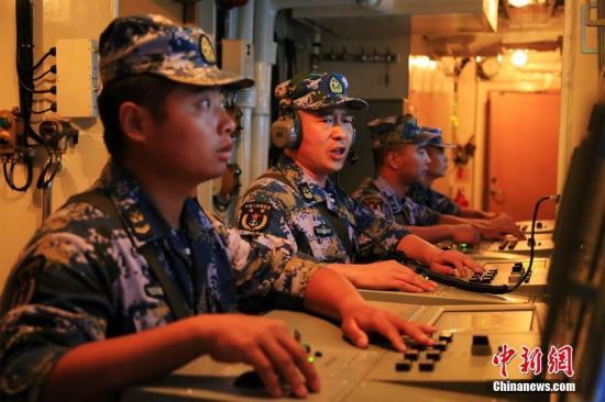 """当地时间9月11日至12日,""""卡卡杜-2018""""多国海军联合演习进入最后的海上红蓝实兵自由对抗阶段,代表中国海军参演的黄山舰在达尔文外海与其他16个国家的舰机共同参演,演习达到预期演练目标。图为黄山舰舰空导弹区队长汪焕辉指挥战位人员进行防空抗击。/p中新社发 徐广 摄"""