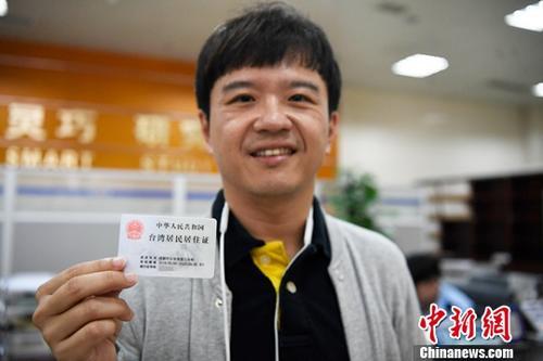 2018年9月13日,在成都師范學院工作五年的臺胞羅天豪從工作人員手中接過臺灣居民居住證。<a target='_blank' href='http://www.dbisr.tw/'>中新社</a>記者 安源 攝