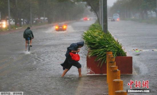 菲律宾民众顶着狂风暴雨出行。