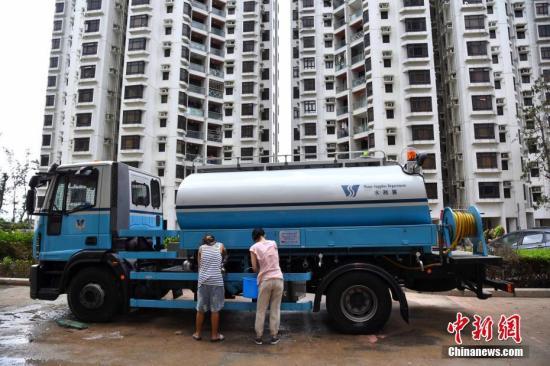 9月17日上午,在强台风山竹吹袭期间水浸严重的杏花�,水务署亦派出水车供水予住户。中新社记者 麦尚�F 摄