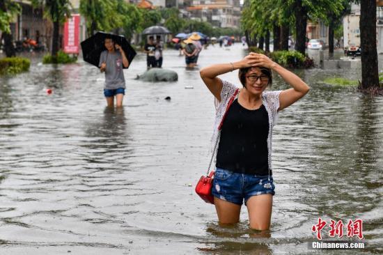 资料图:台风过境民众涉水出行。中新社记者 陈骥�F 摄