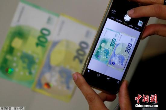 资料图:2018年9月17日,位于德国法兰克福的欧洲央行总部相关负责人向媒体公开展示了新版100欧元和200欧元钞票,并展示了新钞的防伪特征。