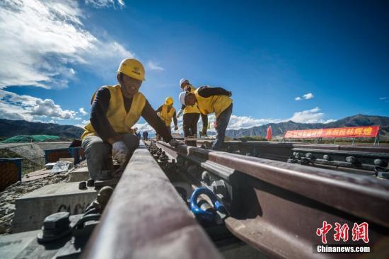 9月16日,川藏铁路拉萨至林芝段首组道岔进行铺设,首组铺设道岔所在地属西藏山南市贡嘎车站,是拉林铁路第一个新建车站,设计新铺设道岔15组,每组道岔长43.2米。川藏铁路建成后将成为继青藏铁路之后连结雪域高原与内地的又一条交通大动脉,其中拉林铁路是在建川藏铁路、待建滇藏铁路的共同路段,是进藏铁路的重要构成段,拉林铁路新建正线铺轨403.14千米,运营长度435.48千米。图为中铁十一局三公司施工人员在川藏铁路拉林段铺设首组道岔。 <a target='_blank' href='http://www.chinanews.com/'>中新社</a>记者 何蓬磊 摄