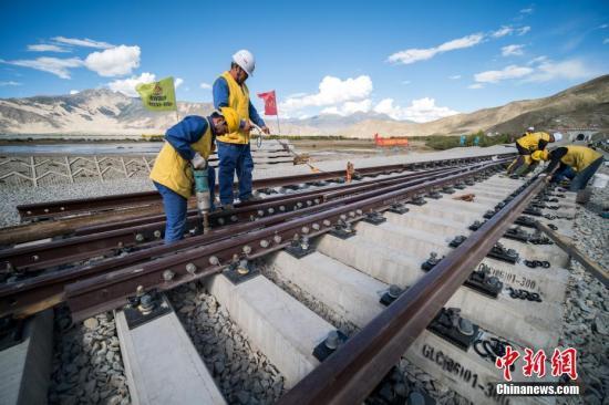 9月16日,川藏铁路拉萨至林芝段始组道岔进走铺设,始组铺设道岔所在地属西藏山南市贡嘎车站,是拉林铁路第一个新建车站,设计新铺设道岔15组,每组道岔长43.2米。图为中铁十一局三公司施工人员在川藏铁路拉林段铺设始组道岔。 中新社记者 何蓬磊 摄