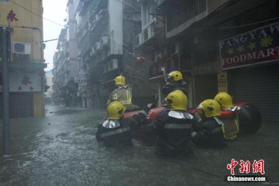 """9月16日,今年第22号台风""""山竹""""强势来袭,给澳门带来狂风暴雨,内港等低洼地带几成泽国,水深及腰。图为消防局出动橡皮艇,沿水浸街道搜索被困居民。 中新社发 钟欣 摄"""