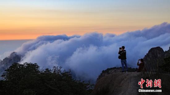 雾浪滚滚,引得游客伫立山头拍照。叶永清 摄