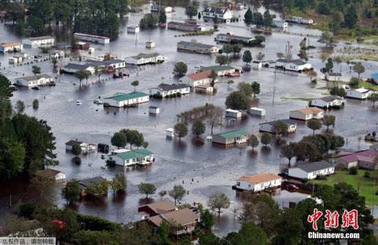 """当地时间9月17日,美国北卡罗来纳州,飓风""""佛罗伦萨""""袭击当地导致内陆成水乡泽国。飓风""""佛罗伦斯""""上周登陆美国北卡罗来纳州后,给当地带来灾难性洪水,目前洪水已蔓延至南卡罗莱纳和北卡罗莱纳州的整个内陆区域。目前,因""""佛罗伦斯""""死亡的人数已攀升至32人,其中24人来自北卡州。"""