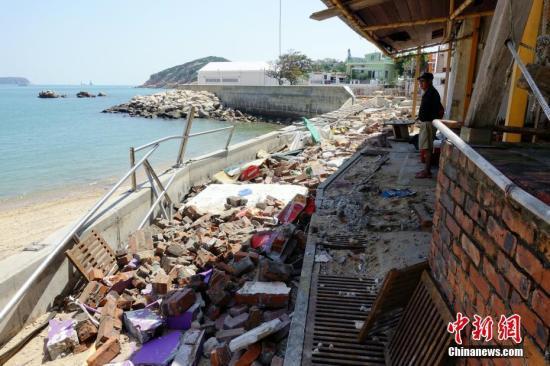 """9月19日,强台风""""山竹""""已经过去三天,但进入香港石澳渔村的道路仍未恢复正常,大巴车依旧停驶。石澳泳滩、后滩泳滩等地满目疮痍,周星驰电影《喜剧之王》里的多个外景地被摧毁,著名的婚纱摄影景点""""蓝桥""""(情人桥)更是被台风引起的风暴潮彻底摧毁,荡然无存。图为位于后滩泳滩旁的酒吧被大浪摧毁,这也是《喜剧之王》中的外景地。<a target='_blank' href='http://www-chinanews-com.cntlp.com/'>中新社</a>记者 张炜 摄"""