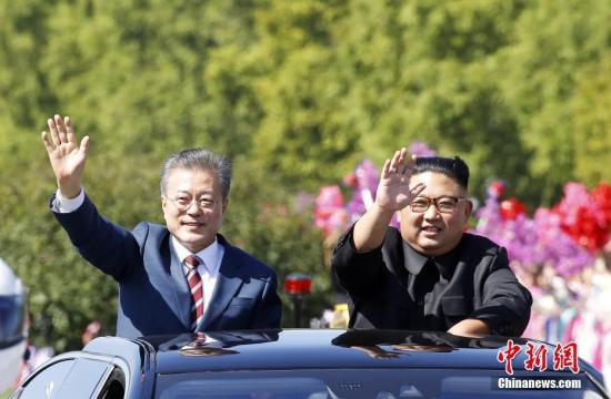 """韩国总统文在寅9月18日抵达朝鲜平壤,今年第三次""""文金会""""将于9月18日至20日举行。18日,文在寅与金正恩一同驱车平壤街头,二人打开天窗,向民众挥手致意。 平壤联合采访团供图"""