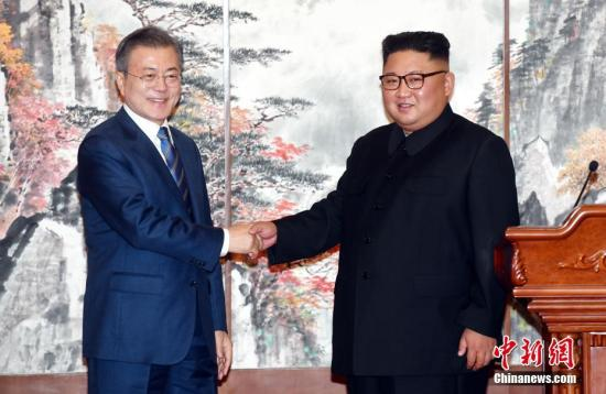 资料图:在朝鲜平壤,朝鲜国务委员会委员长金正恩(右)与韩国总统文在寅在举行共同记者会后握手。中新社发 平壤联合采访团供图