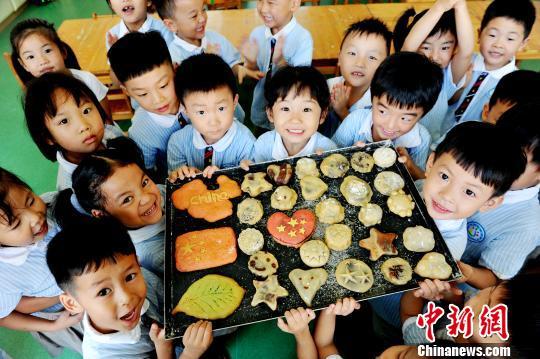 9月20日,江西省德兴市幼儿园小朋友,开心展示出自己亲手制作、童趣十足的月饼,喜迎中秋佳节的到来。 卓忠伟 摄