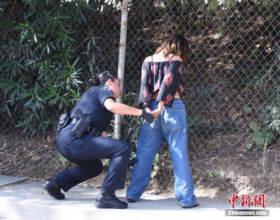 当地时间9月20日下午,美国加利福尼亚州大洛杉矶地区圣盖博市一座社区公园停车场内,当地警方在巡逻中发现可疑车辆并搜出违禁毒品。图为警察检查嫌疑人是否携带武器。<a target='_blank' href='http://www-chinanews-com.do-fineprinting.com/'>中新社</a>记者 张朔 摄
