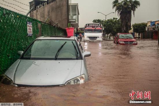 当地时间9月20日,墨西哥暴雨导致库利阿坎街道被淹。图为车辆在积水中行驶。