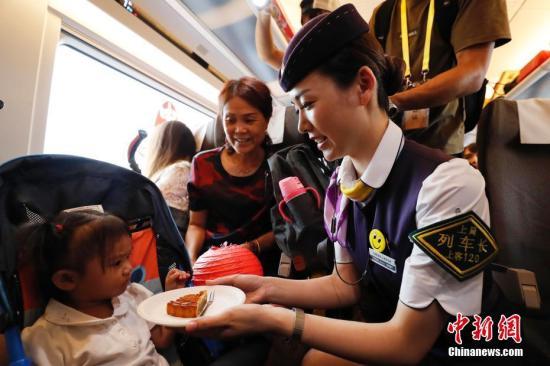 图为G99次列车长为旅客送上月饼。 殷丽勤 摄