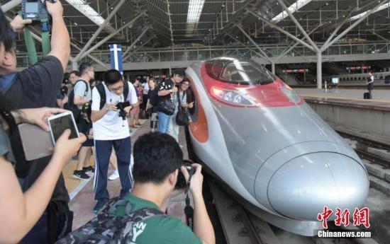 9月23日上午,香港高铁西九龙站正式投入服务,迎接第一批乘客。大批旅客在列车前拍照留影,兴奋迎接高铁新时代。 中新社记者 李志华 摄