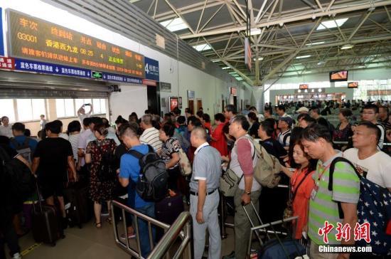 乘客排队检票进站。 王东明 摄
