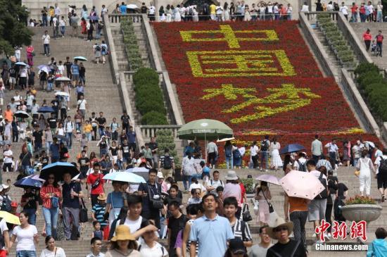 """9月23日,南京中山陵游人众多,游人从鲜花布置的""""中国梦""""字样边经过。 <a target='_blank' href='http://www.chinanews.com/'>中新社</a>记者 泱波 摄"""