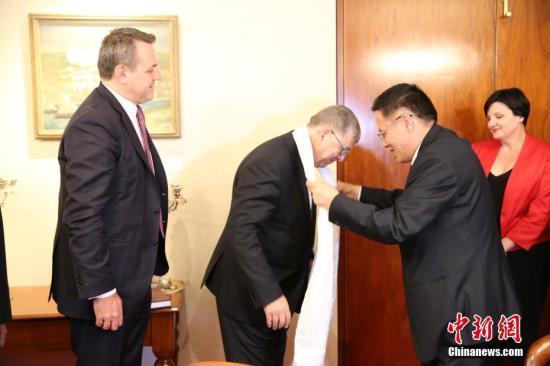 当地时间9月25日,中国全国人大西藏代表团访问悉尼。当天上午,代表团参访新南威尔士州议会。图为代表团团长、西藏自治区人大代表、昌都市人大常委会主任贡秋江村向新南威尔士州上议院议长阿扎卡献哈达。中新社记者 陶社兰 摄