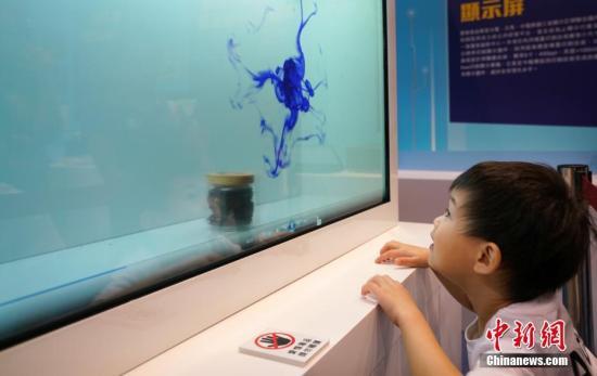 图为一位小朋友被中国国产透明显示屏上播放的逼真画面吸引。<a target='_blank' href='http://www.chinanews.com/'>中新社</a>记者 张炜 摄