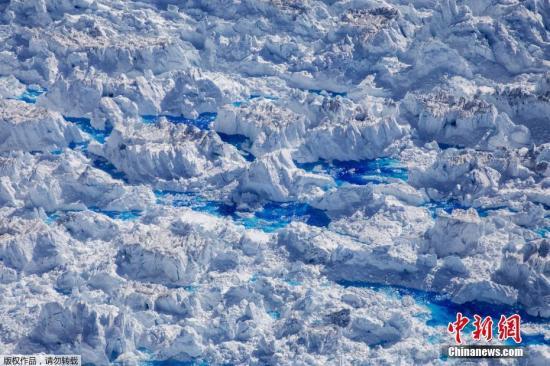 资料图:格陵兰岛塔西拉克附近的黑尔海姆冰川顶部出现的融水池。大气和海洋科学专家大卫·霍兰德和他的团队在这里见证了一个关于北极的重大事件。
