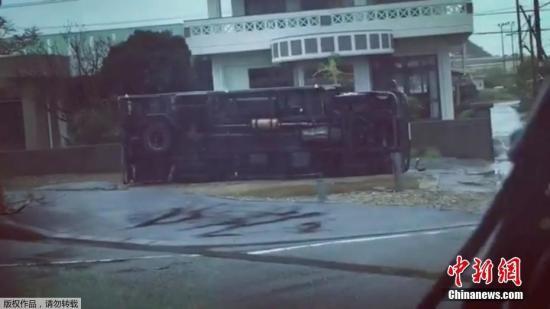 一辆大巴车被掀翻在地。
