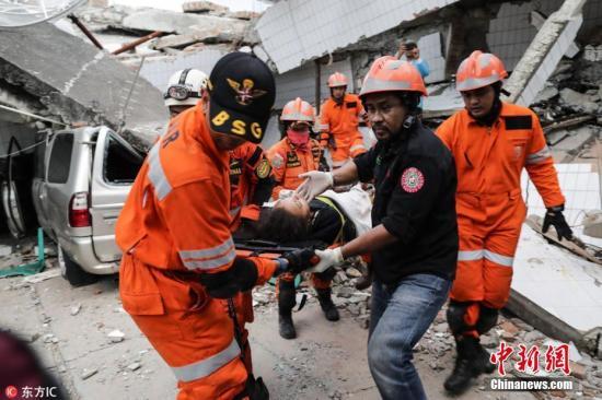 当地时间2018-12-13,印度尼西亚中苏拉威西省帕卢,救援者抬着一名从餐厅废墟下救出的地震幸存者。