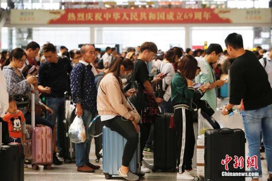 民众在排队等待验票上车。殷立勤 摄
