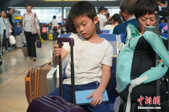 10月1日,小男孩在北京南站内候车时玩弄行李箱。当天是国庆假期首日,北京南站迎来客流高峰。<a target='_blank' href='http://www-chinanews-com.xianyunyehe.net/'>中新社</a>记者 张兴龙 摄