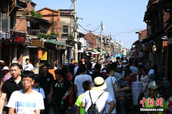 10月1日,国庆黄金周首日,福建泉州西街人潮涌动。西街是泉州最早开发的街道和区域,早在宋朝就已成为泉州繁荣的符号,现为泉州市区保存最完整的古街区,保留着大量具有历史原貌的建筑。<a target='_blank' href='http://www-chinanews-com.scjhfood.com/'>中新社</a>记者 王东明 摄