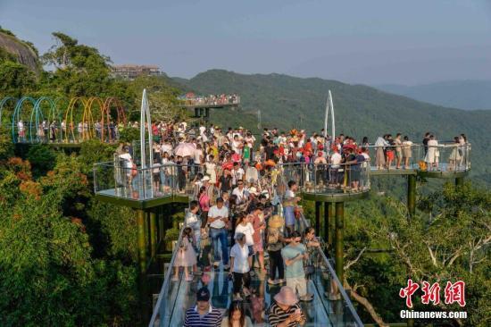 图为游客挤满热带天堂森林公园玻璃栈道。洪坚鹏 摄