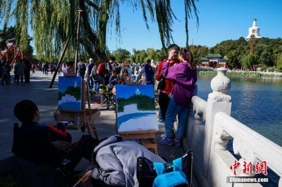 10月6日,北京迎来大风天气。图为学生在北海公园写生。中新社记者 崔楠 摄