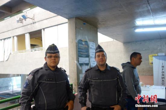 两名警察在巴西圣保罗一个投票站维持秩序。/p中新社记者 莫成雄 摄