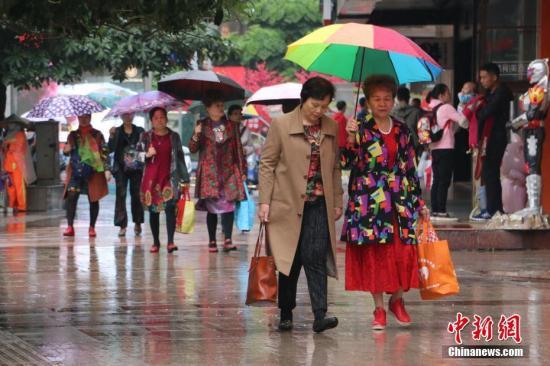 柳州市五星街上民众纷纷换上长袖长裤,抵御寒冷。林馨 摄