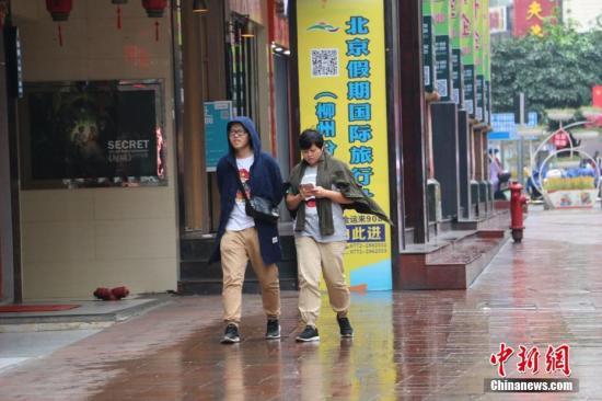 冷空气来袭,民众带上帽子、披着外套御寒。林馨 摄
