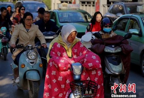 10月10日,河南郑州,受冷空气影响,气温骤降,民众包裹严实出行。中新社记者 王中举 摄